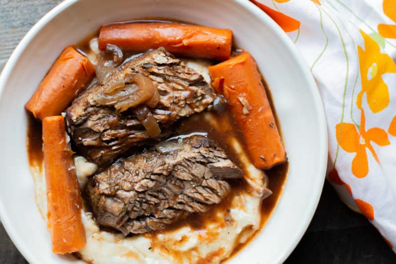Bowl of mashed potatoes with sliced brisket and carrots and sauce.