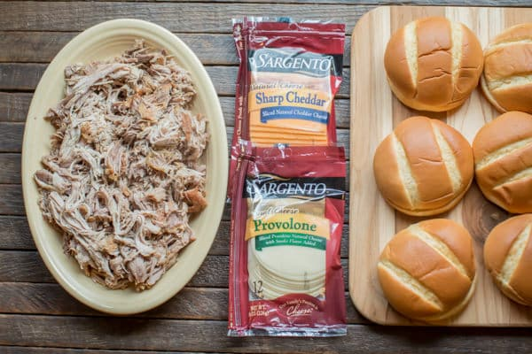shredded pork, cheese, and buns on a cutting board.