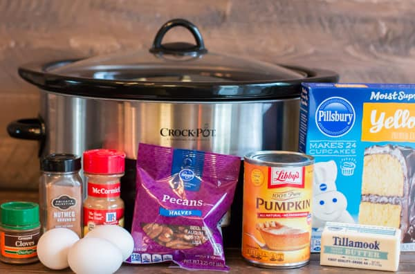 Slow Cooker with pecans, pumpkin, cake mix, cinnamon, nutmeg, eggs and butter in front of slow cooker.