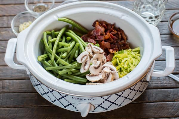 green beans in a slowc cooker with mushrooms, cooked bacon and leeks.