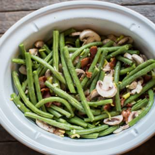 green beans mushrooms and bacon stirred together in a slow cooker.