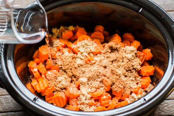 water being poured over carrots in a slow cooker.