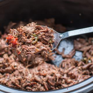 shredded mexican beef on a spoon coming from a slow cooker.