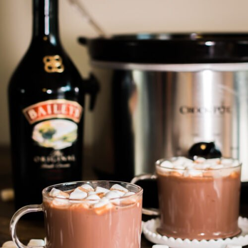 2 cups of baileys hot chocolate with bottle of baileys behind it.
