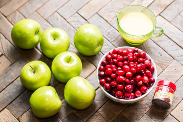 green apples, cranberries and orange juice on a wooden table.