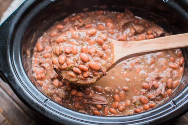 cooked pinto beans on a wooden ladle in  a slow cooker
