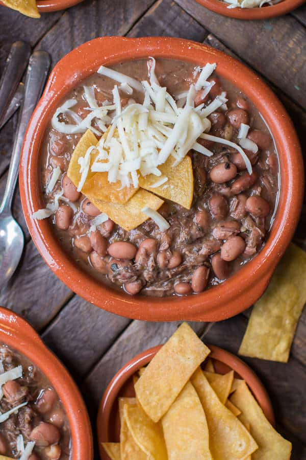 close up of pinto beans and beef with cheese and tortilla strips in it.
