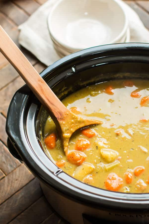 close up of split pea soup in a slow cooker with large wooden ladle in it.