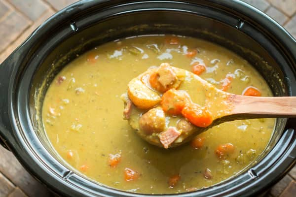 scoop of split pea stew coming from a slow cooker.