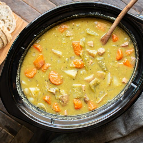 split pea stew in a slow cooker with wooden ladle in it.