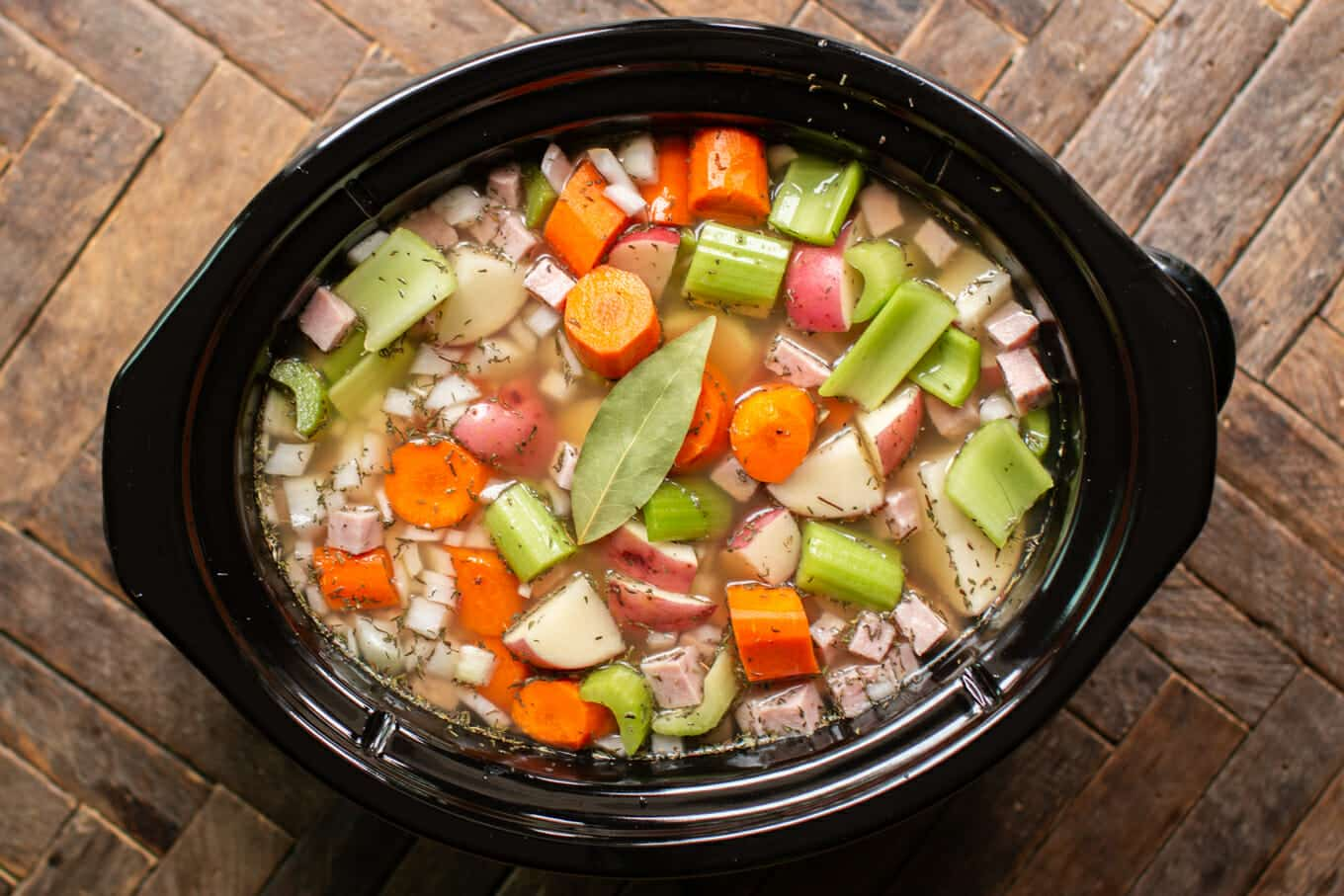 uncooked split pea stew in a slow cooker.