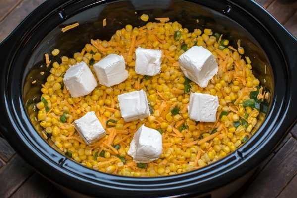 corn in cheese and jalapenos with cream cheese cubes on top.