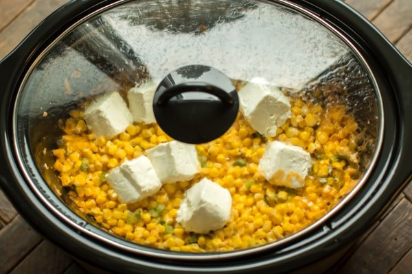 Slow cooker with cooking creamy jalapeno corn in it.
