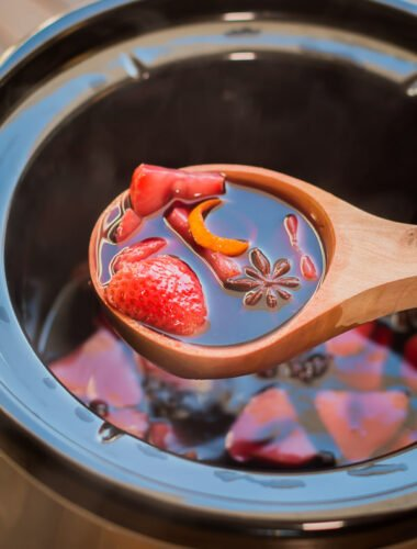 mulled wine in wooden spoon coming from slow cooker.