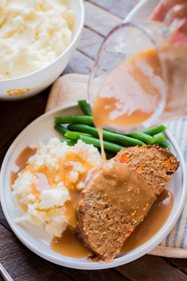 gravy being poured over turkey meatloaf with mashed potatoes and green beans.