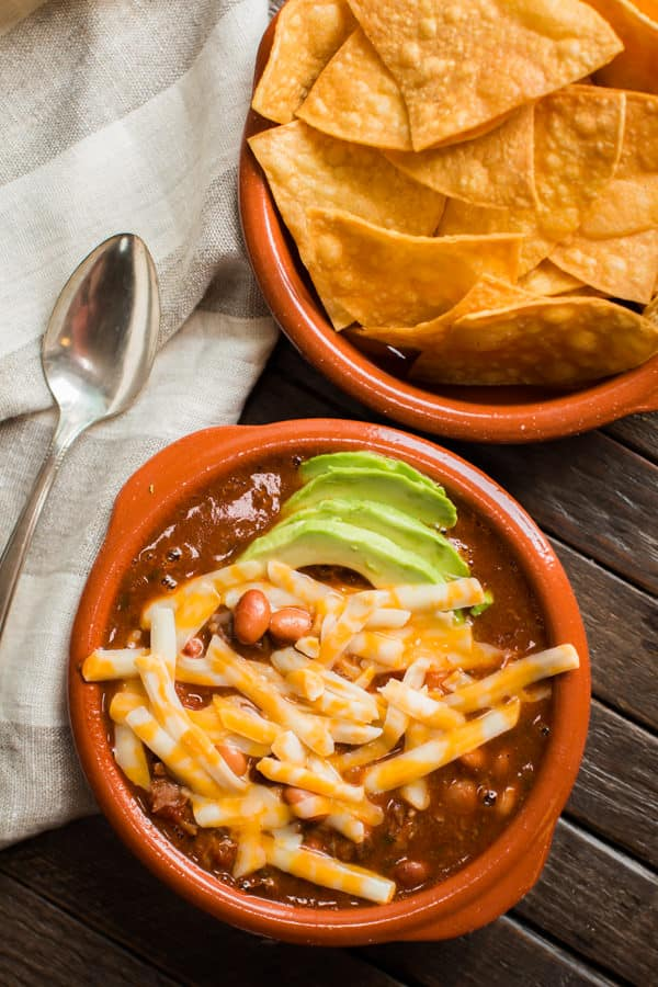 bowl of enchilada chili with cheese and avocado