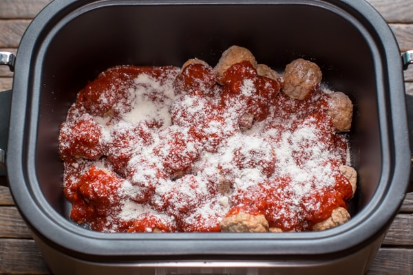 uncooked meatballs with sauce and parmesan cheese.
