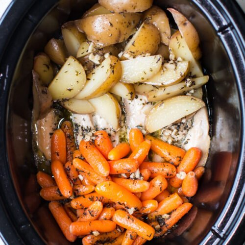 carrots, potatoes, and chicken tenders with buttery garlic sauce in a slow cooker.