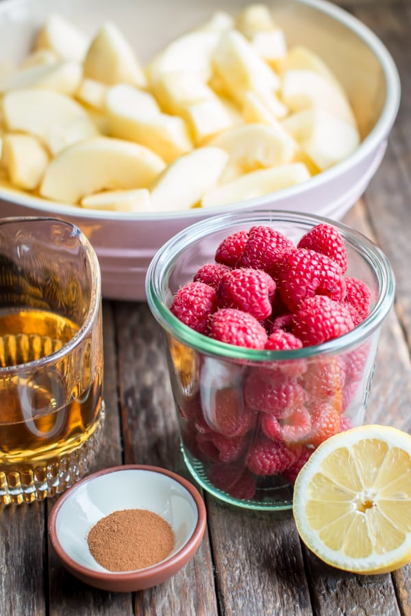 jar of raspberries, bowl of apples, lemon, cinnamon and apple juice on a table.