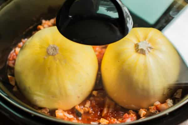 spaghetti squash halves in slow cooker with lid on.