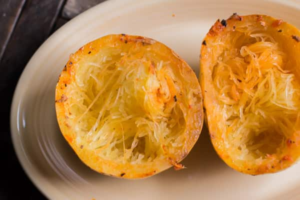 cooked spaghetti squash halves on a platter.