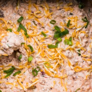 sausage dip with cheese and green onion on top.