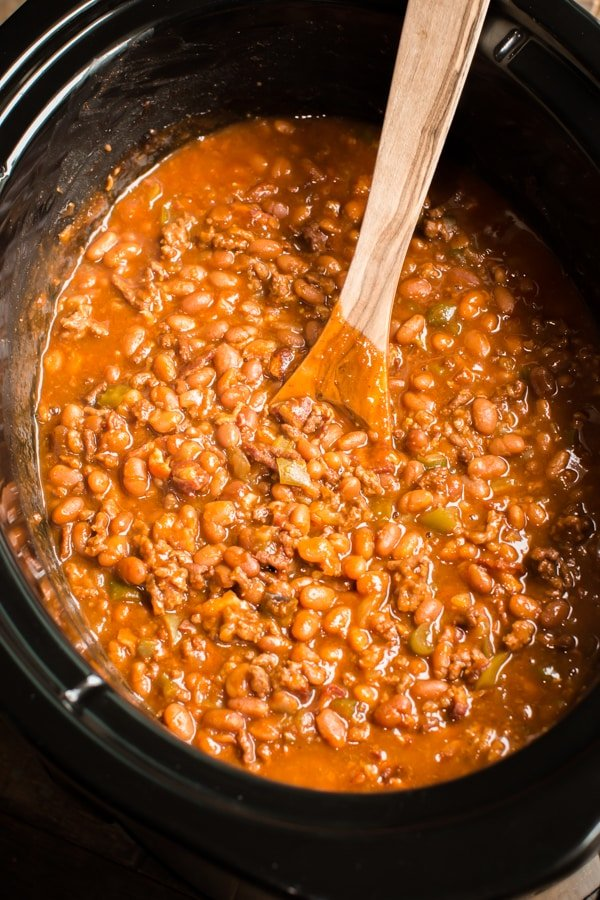 close up of baked beans with a wooden spoon in it.