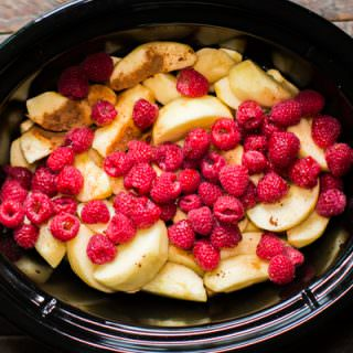 sliced apples, cinnamon and raspberries in a slow cooker.