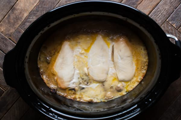 3 chicken breasts in a slow cooker cooked in a cream sauce.