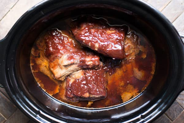 cooked ribs in a slow cooker with barbecue sauce.