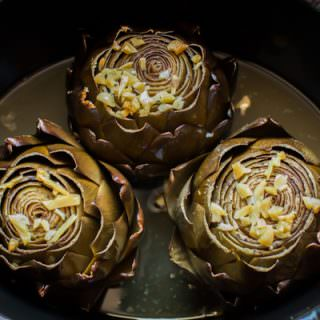 3 artichokes in a slow cooker, done cooking.