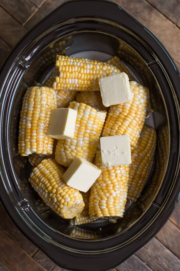 multi color corn in slow cooker with butter on top.