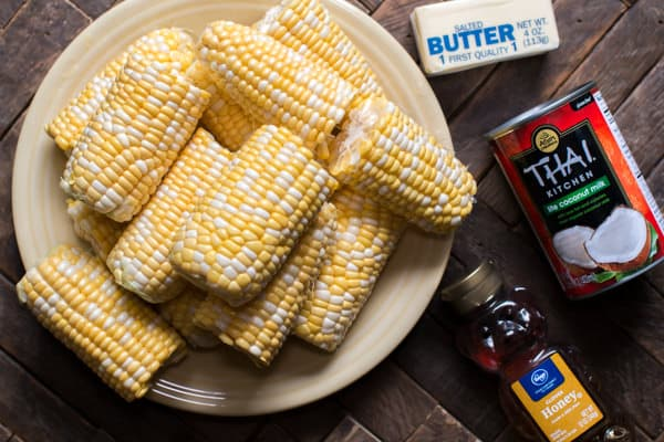Corn on the cob on plate, coconut milk and honey and butter on side.
