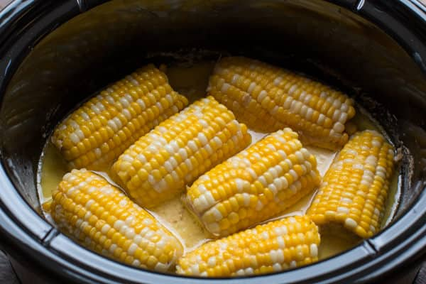slow cooker with corn on the cob in a creamy liquid.