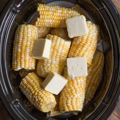 corn on the cob with pats of butter on top in a slow cooker.