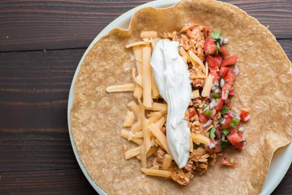 chicken burrito filling with shredded cheese and salsa on a wheat tortilla.