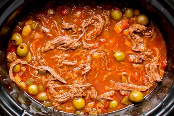 close up of ropa vieja with olives and sauce in the slow cooker.