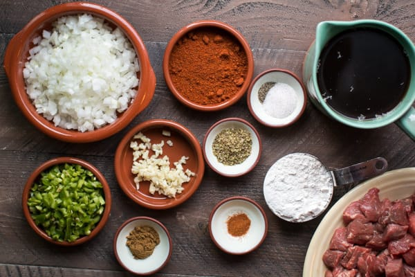 seasonings, broth, flour, jalapeno, onion on a wooden table.
