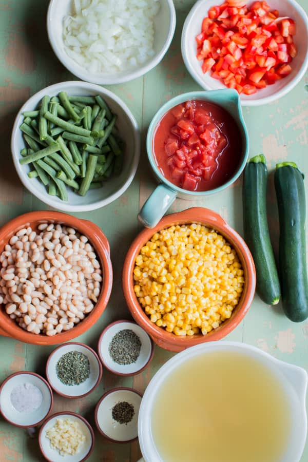 corn, white beans, green beans, tomatoes, broth, seasonings and squash on a table.