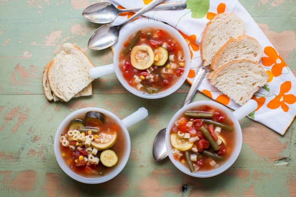 3 bowls of summer minestrone soup on a wooden table.