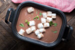 slow cooker full of mint hot chocolte with large marshmallows on top.