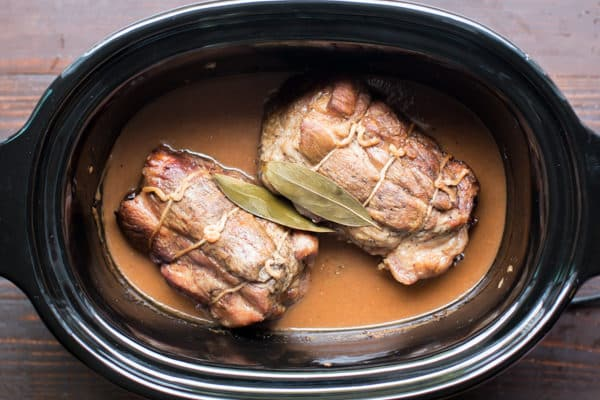 cooked pork roasts in a slow cooker with gravy