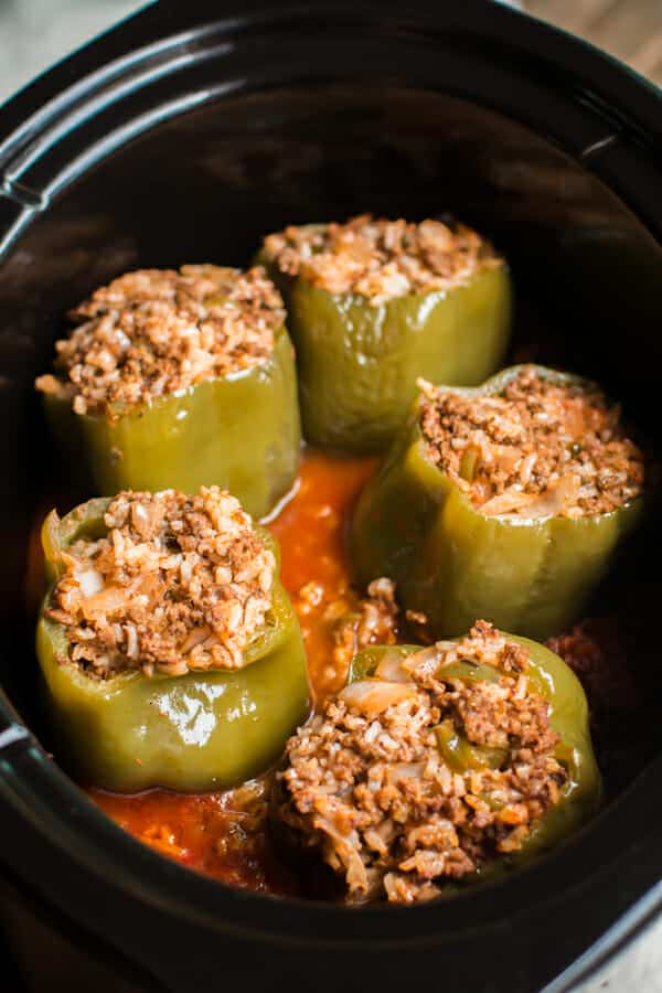 close up photo of 5 stuffed peppers in slow cooker
