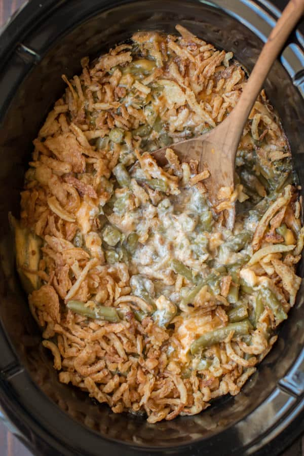 spoon in cheesy green bean casserole in slow cooker.