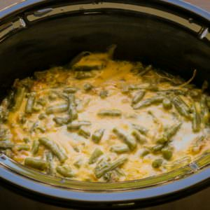close up of cheesy green beans in a slow cooker