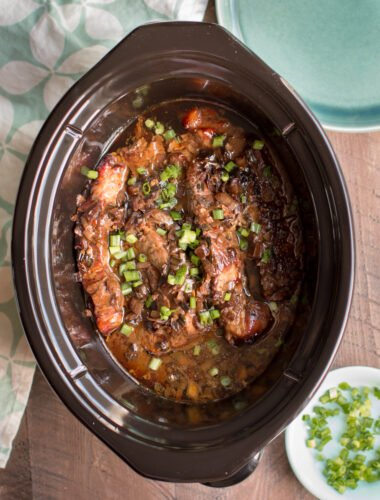 cooked ribs in sauce with green onions on top.
