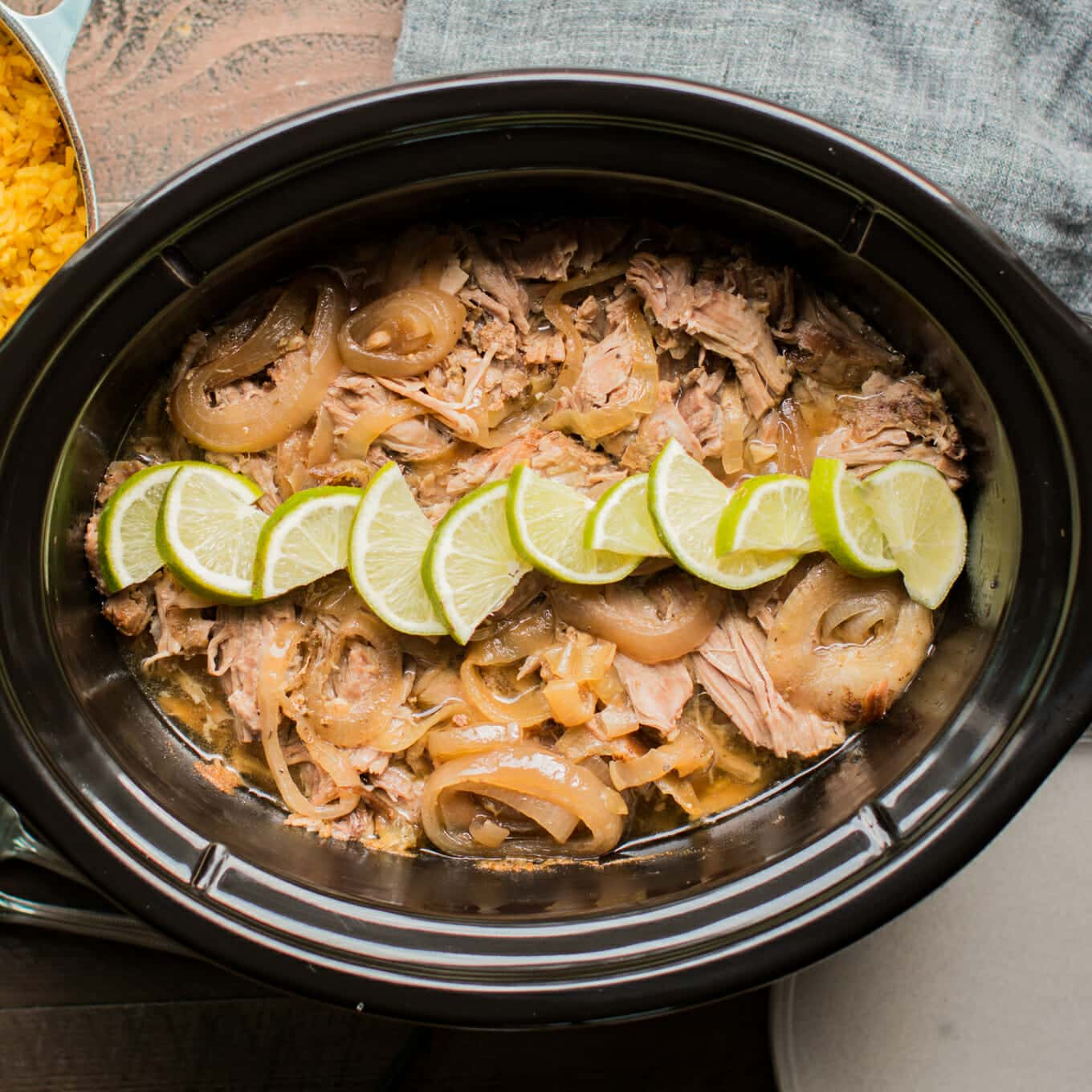 top view of shredded Cuban pork in slow cooker garnished with limes