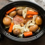 corned beer, cabbage, carrots, and potatoes in slow cooker.
