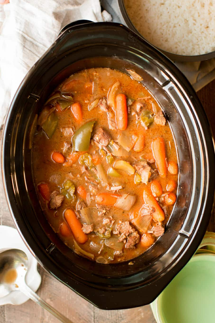 cooked beef stew in slow cooker with carrots and bell pepper