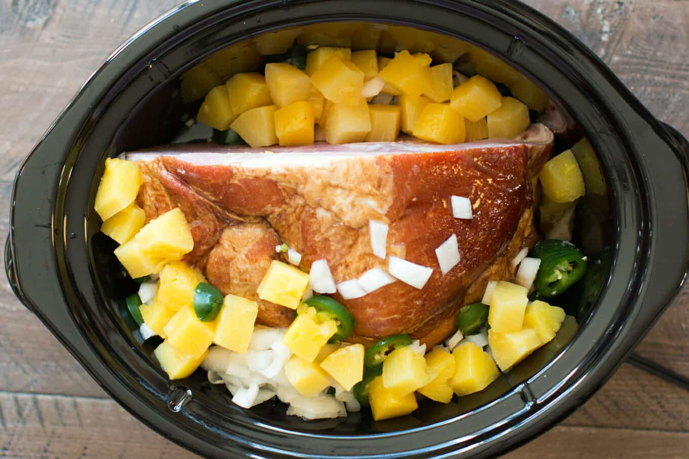 Ham in slow cooker with pineapple, onion and jalapeno on top. Uncooked.